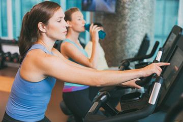 Woman Touching Screen on Exercise Bike in Gym