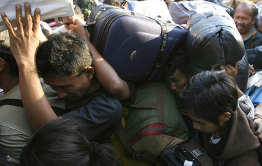 Passengers scramble with their belongings while trying to get onto a ship at Tanjung Perak port in Surabaya