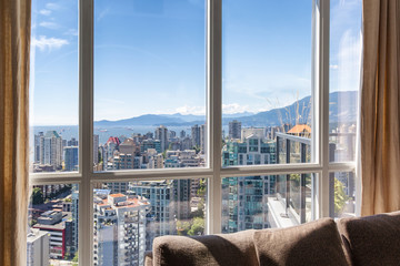 Vancouver, Canada. Penthouse window views of downtown Vancouver skyscrapers, bay and mountains on a sunny day with blue sky. Linen drapes and sofa cushions seen inside.