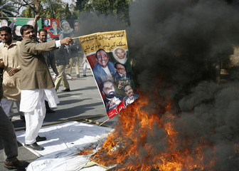 Supporters of Pakistan Muslim league burn a poster featuring President Asif Ali Zardari during a protest against the Supreme court's decision on the disqualification of their leaders in Lahore