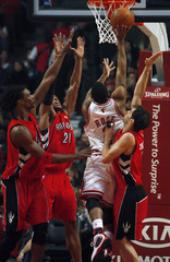Raptors' players defend Bulls' Rose as he drives to the basket in their NBA basketball game in Chicago