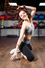 Young smiling fitness woman doing aerobic dance exercise in gym