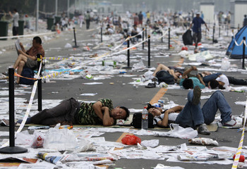 People sleep among rubbish as they wait in a line to buy Olympic tickets at a ticket office near the National Stadium, also known as the Bird's Nest, in Beijing