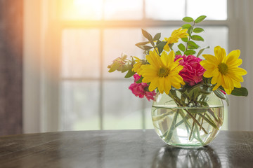 Spring flowers on table in vase with dark greys and blacks with open window fresh concept and copyspace.
