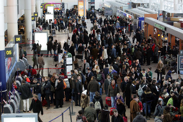 Travellers queue for information at the Brussels National Airport where several flights are cancelled due to heavy snow in Zaventem