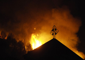 The roof of the St. Nikola church in the village of Kukurecani is silhouetted against a forest fire near the city Bitola