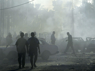 Iraqis walk through a haze of smoke outside an Assyrian church after explosion in Baghdad.