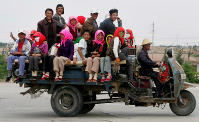 People travel on a tractor at migrant village Hongsibao in Wuzhong