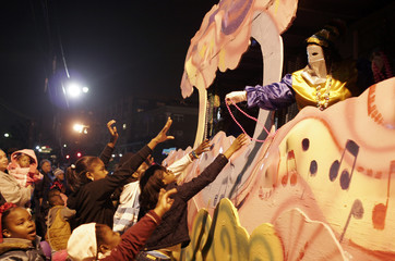 Float riders hand out beads during Mardi Gras parade in New Orleans