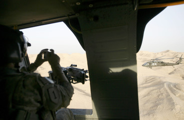 A U.S. soldier takes a picture of a U.S. helicopter flying over Samarra