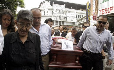 Luz Marina Reyes cries as relatives carry the coffin of her son, Colombian lawmaker Juan Carlos Narvaez, during his funeral in Cali