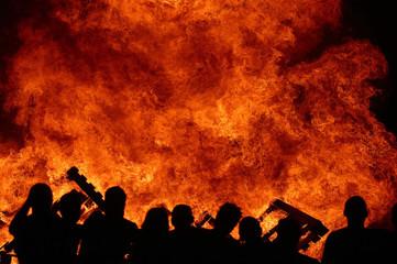 PEOPLE WATCH A BONFIRE DURING TRADITIONAL SAN JUAN'S NIGHT IN TORRE DE BENALGABON.