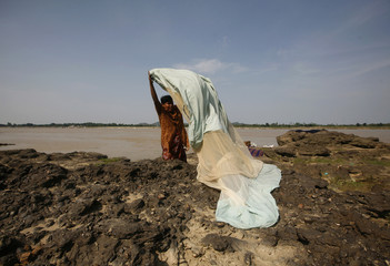 A woman washes clothes for a living along the banks of the Chindwin river in Monywa