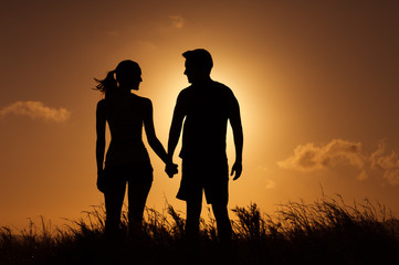Relationship concept. Silhouette of man and woman feeling in love holding each others hands.
