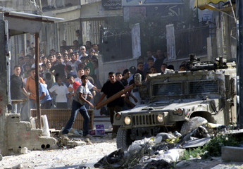 PALESTINIAN YOUTHS HURL STONES AT AN ISRAELI ARMY JEEP DURING CLASHESIN THE BALATA REFUGEE CAMP ...