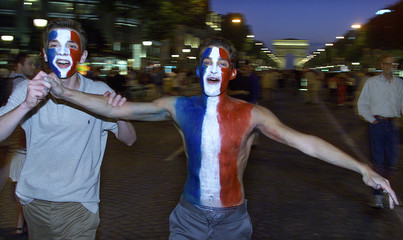A bare chested French soccer fan painted in the French flag colours celebrates on Paris's Champs Ely..