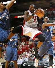 Miami Heat's Dwyane Wade goes up against the defense of Washington Wizards    Etan Thomas and DeShawn Stevenson during first quarter NBA basketball action in Miami