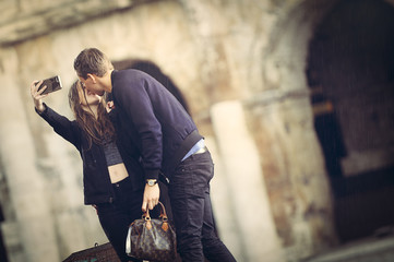 A couple is kissing and taking photos in front of the Coliseum in Rome. November 16 - 2016, Colosseum also known as the Flavian Amphitheatre. Famous world landmark in Rome, Italy