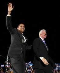 U.S. Democratic Presidential nominee  Obama walks onstage with former President  Clinton at a campaign rally in Kissimmee