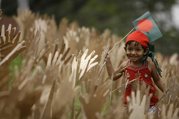 A child plays with a national flag at a place decorated in celebaration of 38th Bangladesh's independence annivery in Dhaka.