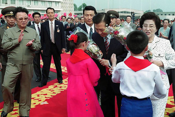 KIM JONG-IL CLAPS AS KIM DAE-JUNG AND WIFE RECEIVE FLOWER BOUQUETS AT PYONGYANG AIRPORT.