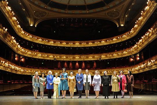 The wives of global leaders attending the G20 summit pose for a photograph on stage at The Royal Opera House central London