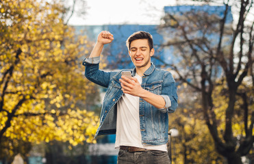 Young man standing outdoors holding mobile phone