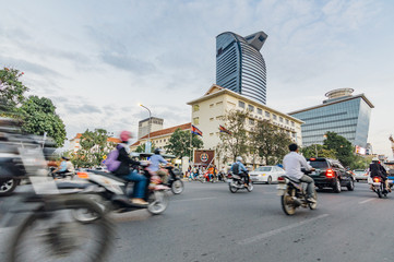 People driving motorbikes on the street in Phnom Penh, Cambodia. Modern skyscrapers on the background