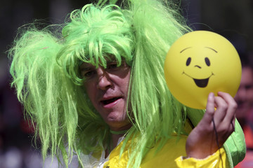 A festival-goer is seen with a smiley face balloon at the Les Vieilles Charrues music Festival in Carhaix