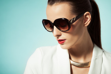 Fashion beauty portrait of female wearing sunglasses and red lipstick.