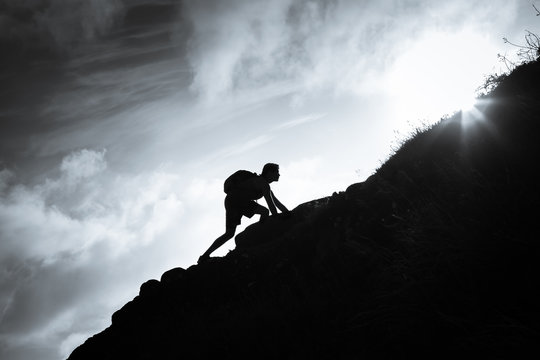 Success, life goals, and taking risk concept. Man climbing up a edge of a mountain.