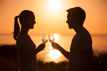 Young romantic couple enjoying a glass of wine together on the beach.