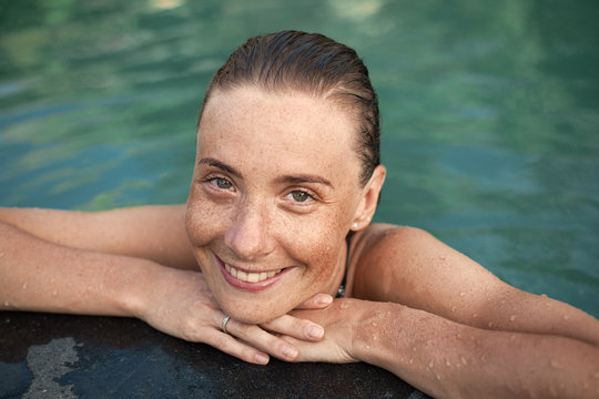 Horizontal close-up portrait of smiling beautiful girl with freckles and wet hair in water, arms on pool edge