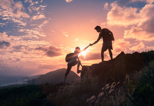 Team work, life goals and self improvement  concept. Man helping his female climbing partner up a steep edge of a mountain.