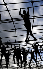 Competitors manoeuvre through a cargo net during the Tough Guy event in Perton