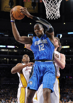Orlando Magic's Dwight Howard gathers a rebound as Los Angeles Lakers Andrew Bynum and Pau Gasol of Spain trail during Game 2 of NBA Finals in Los Angeles