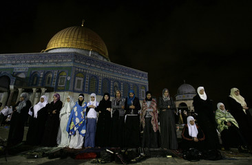 Palestinian women pray during Lilat al-Qader in front of the Dome of the Rock in Jerusalem's Old City