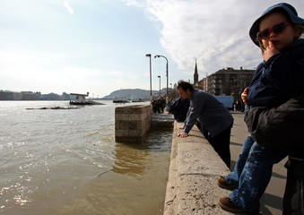Hungarians watch the flooding Danube river in the centre of Budapest