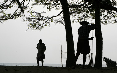 A disabled man walks on the seashore as a fisherman sweeps the beach in the early morning hours in Batticaloa