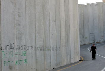 A Palestinian woman walks along the controversial Israeli barrier in Abu Dis
