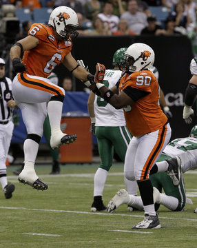 Lions' Glatt and Hunt celebrate after sacking Roughriders' quarterback Bishop during first half CFL action in Vancouver