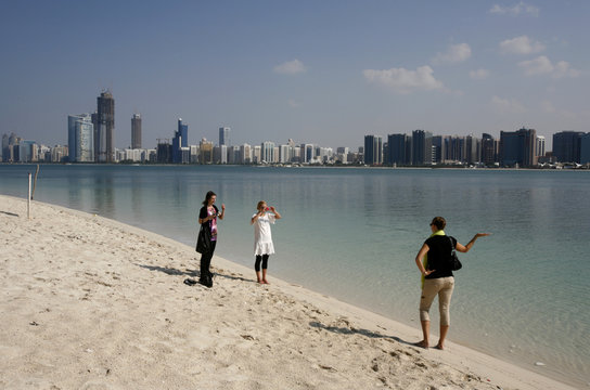 A tourist takes a photograph in front of skyline of Abu Dhabi