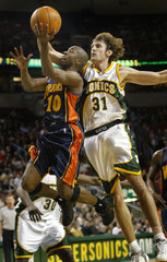WARRIORS SPEEDY CLAXTON DRIVES TO HOOP AGAINST SONICS BRENT BARRY.