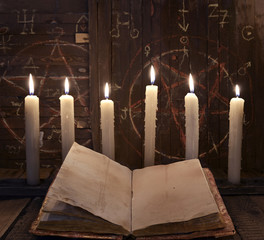 Black magic ritual with burning candles and open book against wooden background.