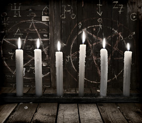 Still life with burning candles on wooden background with pentagram