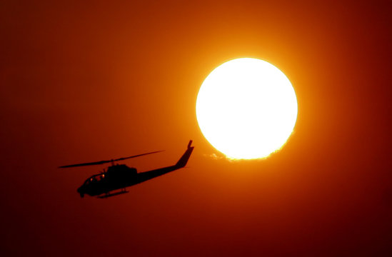 United States Forestry helicopter is silhouetted against the setting sun at the site of the Day fire near Lockwood, California