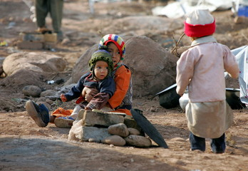 A Kashmiri boy comforts his brother at an evacuation camp in earthquake-devastated Muzaffarabad, the..