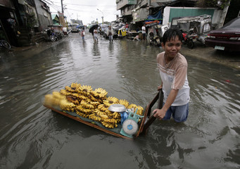A banana vendor turns back after attempting to make his way down a flooded street in flood prone Malabon district after a night of heavy rains hit Manila