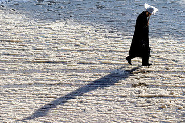 AN ULTRA-ORTHODOX JEW WALKS THROUGH THE SNOW NEAR WESTERN WALL IN JERUSALEM'S OLD CITY.