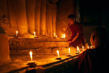 Novices praying with candles in front of buddha statue inside old pagoda, Bagan Myanmar